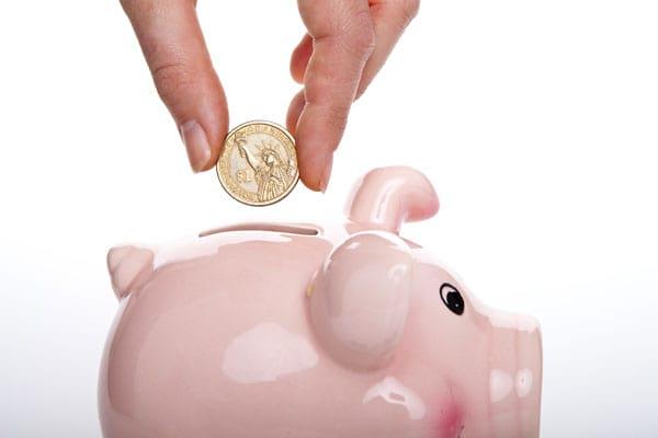 Geld wird in eine Sparschwein gesteckt